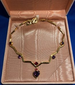 YVES SAINT-LAURENT necklace gilded metal with faceted stones and a central heart stone